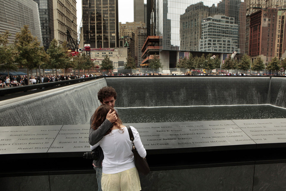 Daniel Jones, who lost his brother, Christopher Carstenjen, holds Rebecca Moss at the place where his brother's name is inscribed on the Sept. 11 memorial at the World Trade Center site in New York during a ceremony to mark the 10th anniversary of the 9/11 attacks Sunday, Sept. 11, 2011. (AP Photo/Carolyn Cole, Pool)