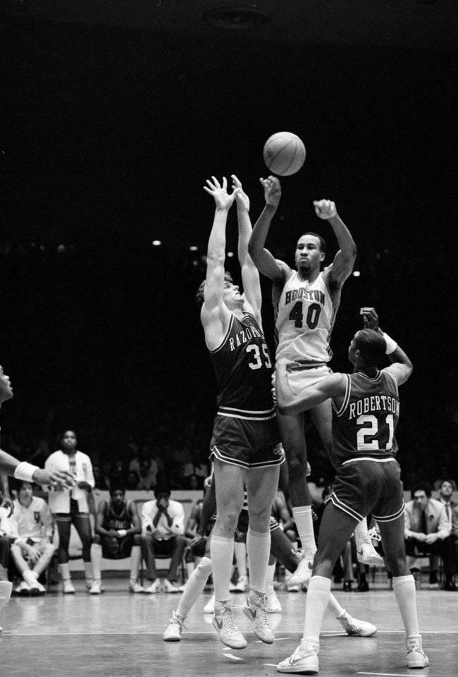 Photo - COLLEGE BASKETBALL: University of Houston's Larry Micheaux (40) is surrounded by Arkansas Razorbacks' Joe Klein (35) and Alvin Robertson (21) and decides to pass the ball during the first half of the Southwestern Conference in Houston, Jan. 22, 1983. (AP Photo/F. Carter Smith)		ORG XMIT: APHS54327