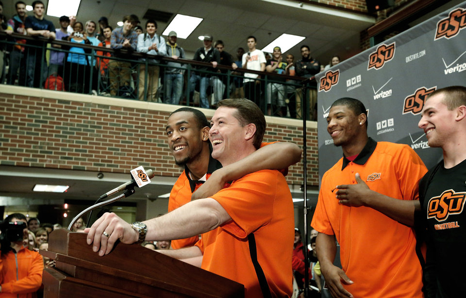 Photo - Coach Travis Ford smiles when one of his returning players, Markel Brown hugsOSU basketball players Le'Bryan Nash, Markel Brown and Marcus Smart delighted  fans when they announced at a noontime press conference they intend to return for another season as members of the Cowboys basketball team. Cheering fans lined all levels in the Student Union atrium Wednesday, April 17, 2013.    by Jim Beckel, The Oklahoman.