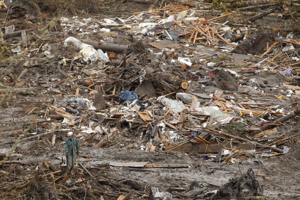 Photo - A searcher walks near a massive pile of debris at the scene of a deadly mudslide, Thursday, March 27, 2014, in Oso, Wash. The death toll is expected to rise considerably within the next two days as the Snohomish County Medical Examiner's Office catches up with the recovery effort, Snohomish County District 21 Fire Chief Travis Hots said Thursday. (AP Photo/The Herald, Mark Mulligan, Pool)
