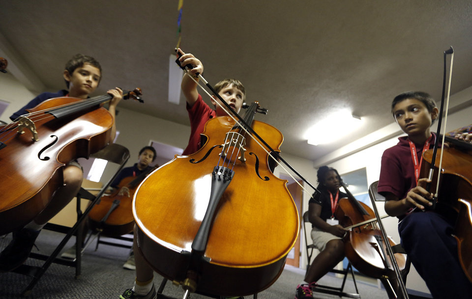 Photo - Ryan McLaughlin, Elliott Miller, and Ricardo Rojas learn to play the cello during a session of a new after-school music program called El Sistema Oklahoma under way at Trinity Baptist International Church, 1329 NW 23. The program is a colloborative effort of St. Luke's United Methodist Church, Oklahoma City University and the Foundation for Oklahoma City Public Schools.  SARAH PHIPPS - SARAH PHIPPS