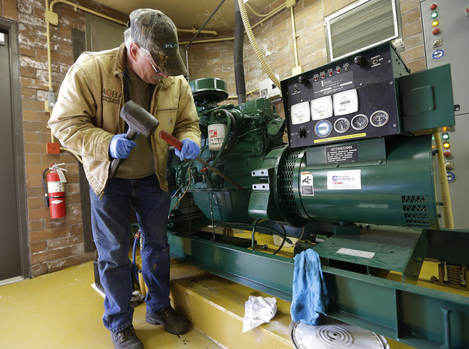 Photo - Jerry Fulbright, a maintenance worker for the city of Hoquiam, Wash., changes a gasket, Monday, March 18, 2014, on an electric generator that will power sewer and groundwater pumps in the event of a power failure. Most of Hoquiam is in a flood plain, and the mayor says despite the pumps and other measures used to reduce the town's risk of flooding, possible increases in federal flood insurance rates would adversely affect many who live here. (AP Photo/Ted S. Warren)