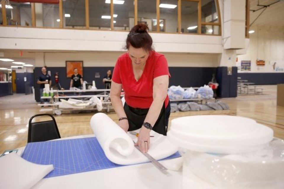 Photo -  SSM Health St. Anthony employee Tricia Woods cuts foam as she and other employees from SSM Health St. Anthony and Santa Fe Family Life Center make face shields inside a gymnasium at Santa Fe Family Life Center in Oklahoma City, Thursday, April 2, 2020. [Bryan Terry/The Oklahoman]
