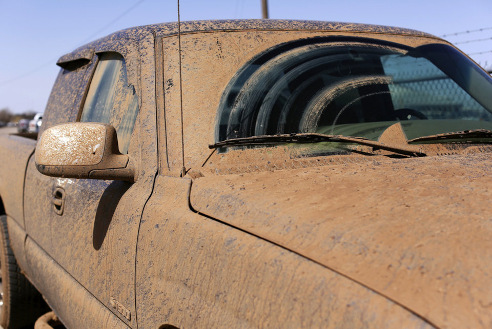 Photo - A mud-covered truck in the parking lot at the Oklahoma Youth Expo at State Fair Park on Tuesday,   March 18, 2014.  Photo by Jim Beckel, The Oklahoman