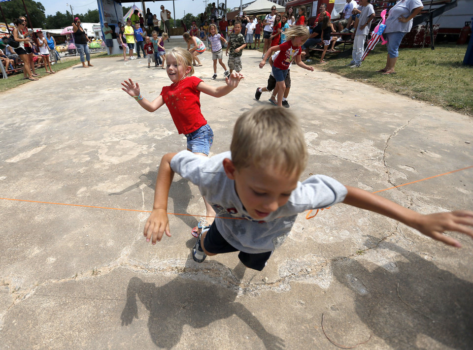 Austin McKedy, 6, falls into the finish line as Lexie Geissler, 6, follows behind during the three-legged race at the Blackberry festival in McLoud, Okla., Saturday, July 7, 2012. Photo by Sarah Phipps, The Oklahoman