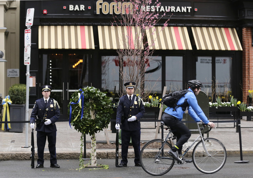 Photo - A Boston Police honor guard is posted outside the Forum restaurant, the site of the second of two bombs that exploded near the finish line of the 2013 Boston Marathon, Tuesday, April 15, 2014 in Boston. Three were killed and more than 260 injured in last year's explosions near the finish line of the race. (AP Photo/Charles Krupa)