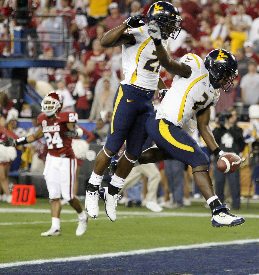 Photo - West Virginia's Dorrell Jolloh (21) and Darius Reynaud (2) celebrate after Reynaud's touchdown during the first half of the Fiesta Bowl college football game between the University of Oklahoma Sooners (OU) and the West Virginia University Mountaineers (WVU) at The University of Phoenix Stadium on Wednesday, Jan. 2, 2008, in Glendale, Ariz. 