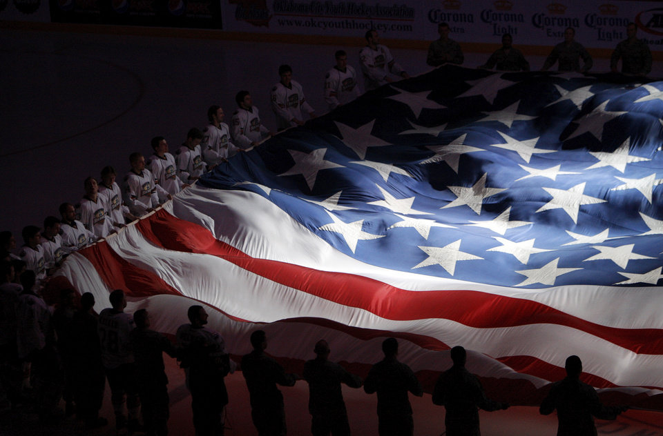 Photo - Hockey players and members of the military hold a giant American flag as part of military appreciation night at before an AHL hockey game between the Oklahoma City Barons and the Grand Rapids Griffins at the Cox Convention Center in Oklahoma City, Saturday, March 24, 2012. Photo by Nate Billings, The Oklahoman