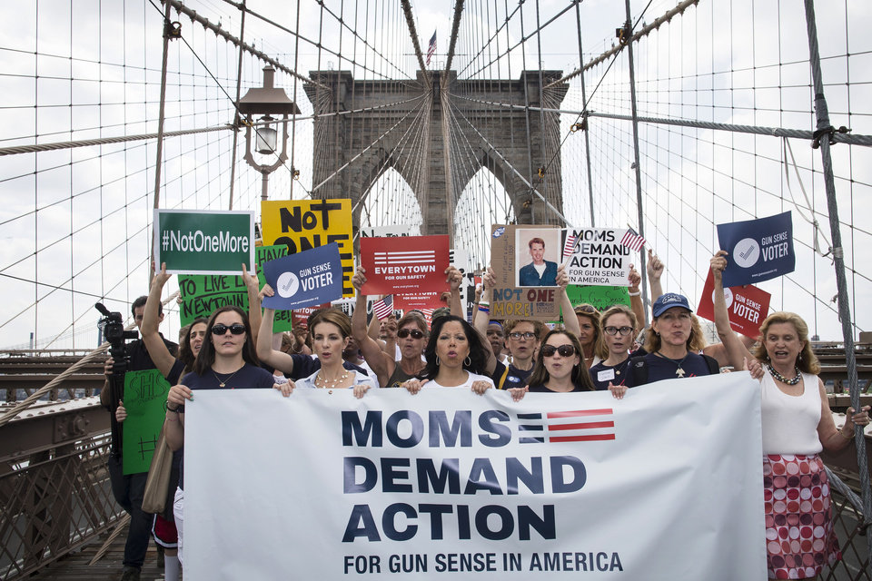 Photo - Hundreds of demonstrators march across the Brooklyn Bridge to call for tougher gun control laws, Saturday, June 14, 2014, in New York. The protest was underwritten by former New York Mayor Michael Bloomberg, one of the most visible gun control advocates in the U.S., and included relatives of some of those slain in the 2012 shooting rampage at Sandy Hook Elementary School in Newtown, Conn. (AP Photo/John Minchillo)