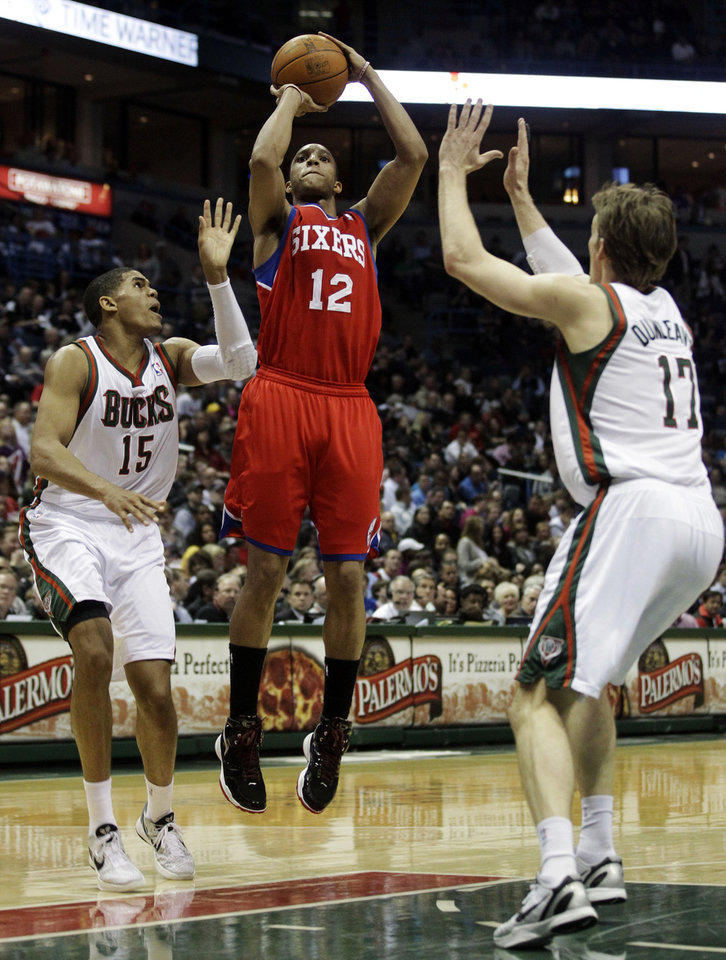 Photo -   Philadelphia 76ers' Evan Turner (12) shoots between Milwaukee Bucks' Tobias Harris (15) and Mike Dunleavy (17) during the first half of an NBA basketball game, Wednesday, April 25, 2012, in Milwaukee. (AP Photo/Morry Gash)