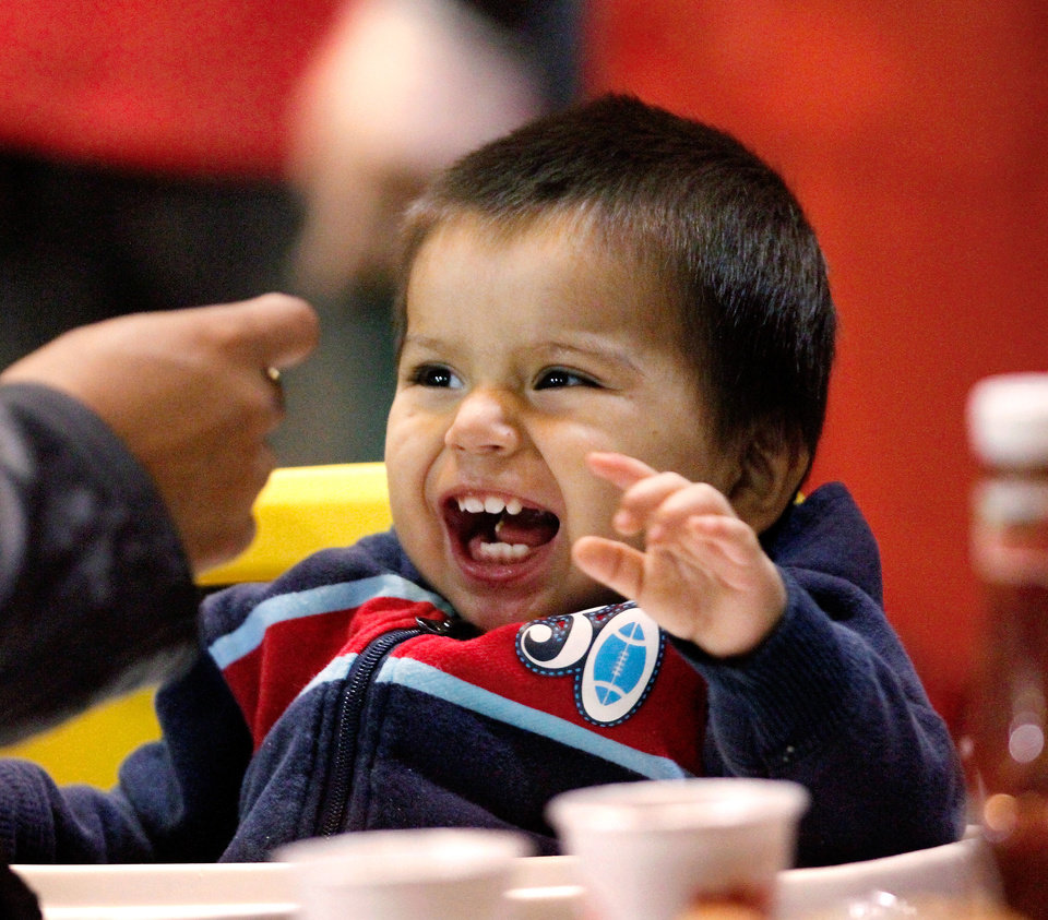 Photo - One year-old Hector Jaramillo laughs when his father brings a spoon with food toward him. Hector was at the brunch with his parents, siblings, an aunt and cousins.  Salvation Army spokesperson Heidi Brandes said more than 1,000 guests were served a hot meal at the  Thanksgiving brunch by volunteers in the Coca-Cola Bricktown Events Center .Thursday morning,  Nov. 24, 2011.  Diners were served eggs, sausage, hash brown potatoes, biscuits and gravy, juice and coffee. Donuts, donated by Krispy Kreme, were also offered to guests. Photo by Jim Beckel, The Oklahoman   Photo by Jim Beckel, The Oklahoman