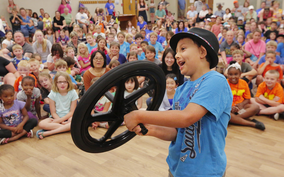 Photo -  Ethan Narramore, 7, holds a spinning wheel that affects his movements during Physics Fun House at the Norman Public Library. PHOTO BY JIM BECKEL, THE OKLAHOMAN   Jim Beckel -