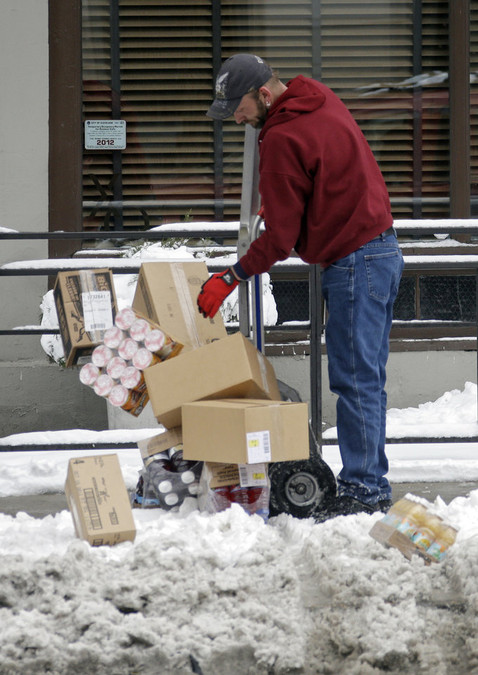 Photo - A delivery man loses his cargo trying to negotiate snow and slush along West Sixth St. in downtown Cleveland Thursday, Dec. 27, 2012. Ohioans picked their way around snow and slush left from the winter's biggest storm so far, with one major interstate still closed for commuters after an evening accident. (AP Photo/Mark Duncan)