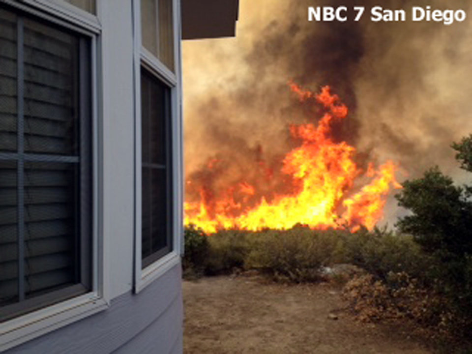 Photo - In this still frame from video provided by KNSD-TV, flames near a home as crews scrambled to corral a wildfire that burned two homes near the San Diego County mountain town of Julian in Southern California Thursday, July 3, 2014. The blaze erupted around 10:30 a.m. and prompted the mandatory evacuation of 200 homes. Firefighters attacked the 150-acre blaze in the air and on the ground. The fire destroyed two homes and an outbuilding and was 15 percent contained at nightfall, state fire Capt. Kendal Bortisser said. (AP Photo/KNSD-TV)