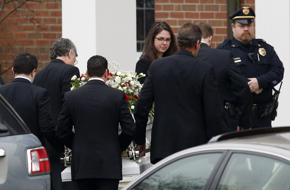 Photo - Pallbearers carry the casket containing the body of James Mattioli into St. Rose of Lima Roman Catholic Church for funeral services,  Tuesday, Dec. 18, 2012, in Newtown, Conn. Mattioli, 6, was killed when Adam Lanza walked into Sandy Hook Elementary School in Newtown, Conn., Dec. 14,  and opened fire, killing 26 people, including 20 children, before killing himself.(AP Photo/Julio Cortez)