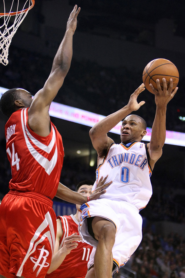 Photo - OKLAHOMA CITY THUNDER NBA BASKETBALL: Russell Westbrook drives in against Houston's Carl Landry during the Thunder - Rockets  game January 9, 2009 in Oklahoma City.      BY HUGH SCOTT, THE OKLAHOMAN ORG XMIT: KOD
