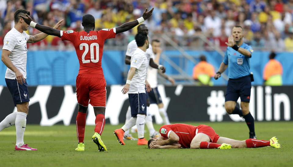 Photo - Switzerland's Johan Djourou (20) signals to referee Sander Van Roekel, of the Netherlands, as Steve von Bergen lies on the ground after getting hit by France's Olivier Giroud during the group E World Cup soccer match between Switzerland and France at the Arena Fonte Nova in Salvador, Brazil, Friday, June 20, 2014. (AP Photo/Natacha Pisarenko)