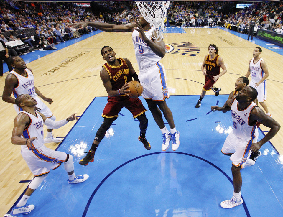 Cleveland Cavaliers guard Kyrie Irving (2) shoots as Oklahoma City Thunder forward Serge Ibaka (9) defends during the fourth quarter of an NBA basketball game in Oklahoma City, Sunday, Nov. 11, 2012. Oklahoma City won 106-91. (AP Photo/Sue Ogrocki)