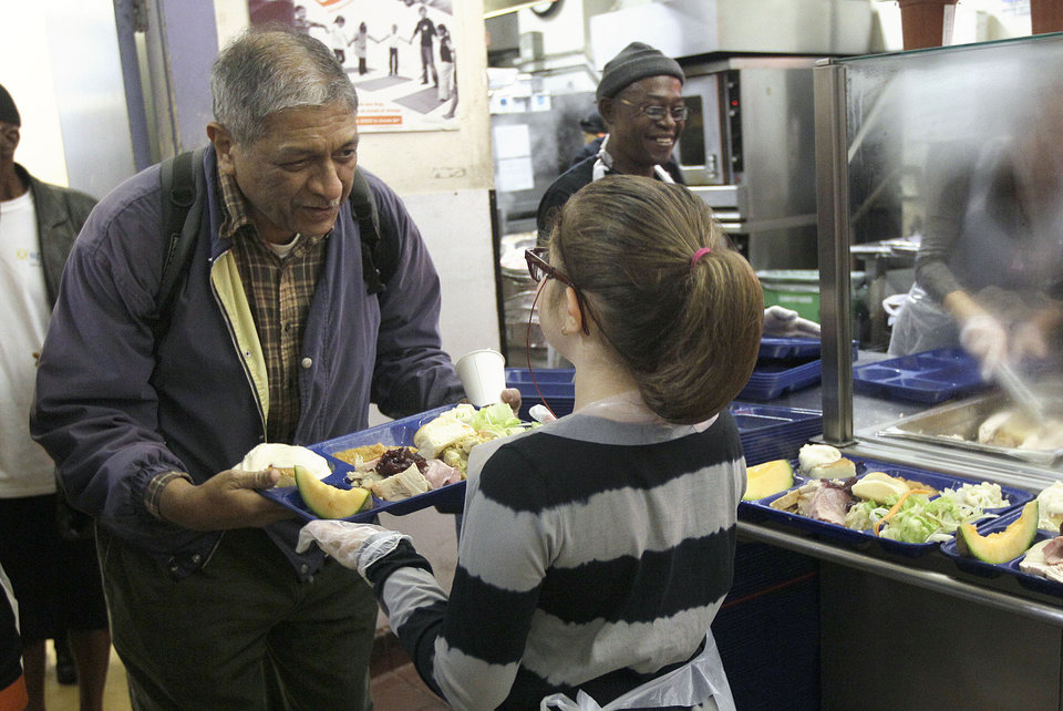 Photo -   Volunteer Madison Errett, 9, hands out a Thanksgiving meal to a man who wished to remain unidentified at the GLIDE foundation in San Francisco, Thursday, Nov. 22, 2012. GLIDE staff estimated that about 500 volunteers helped prepare and serve around 5,000 meals. (AP Photo/Jeff Chiu)