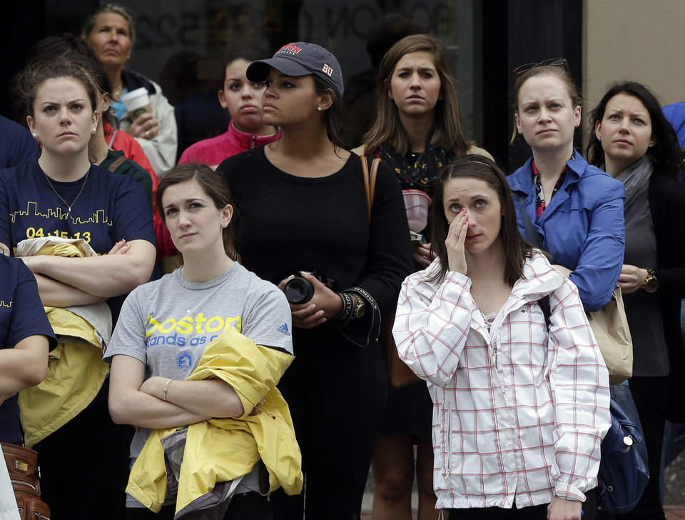 Photo - Heather McDade, of Boston, right, reacts while watching a tribute ceremony with others on an over-sized outdoor monitor, Monday, April 14, 2014, on Boylston Street, in Boston. The ceremony is being held for those killed and injured in the bombings at the finish line of the Boston Marathon a year ago. (AP Photo/Steven Senne)