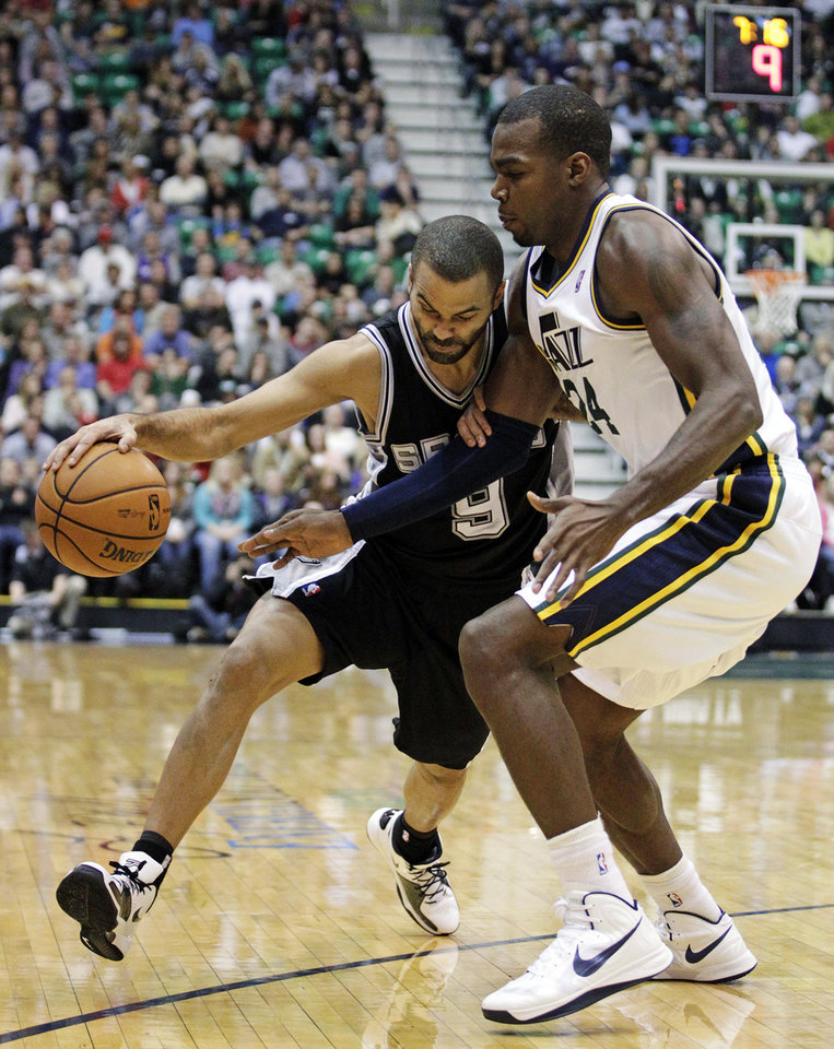 Photo - Utah Jazz forward Paul Millsap (24) defends against San Antonio Spurs point guard Tony Parker (9) in the second quarter during an NBA basketball game, Wednesday, Dec. 12, 2012, in Salt Lake City. (AP Photo/Rick Bowmer)