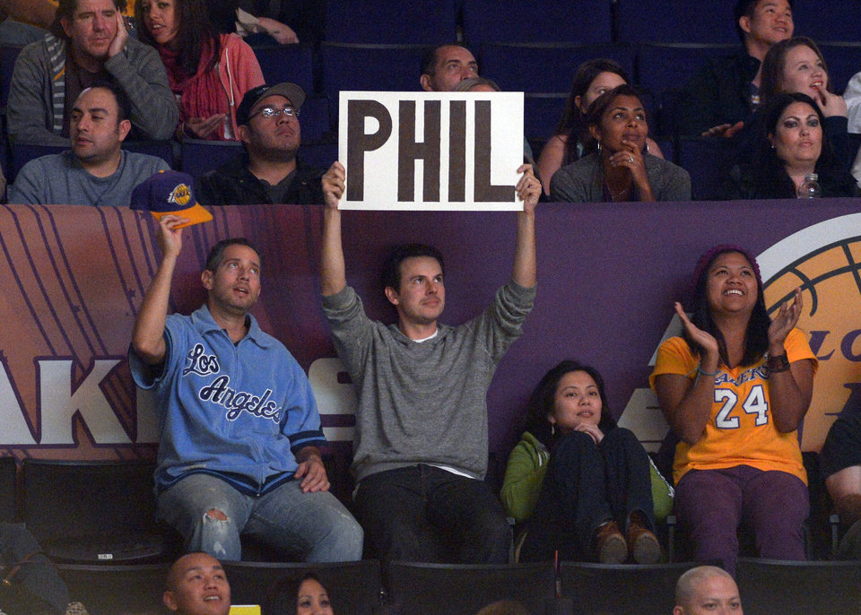 A fan holds up a sign for Phil Jackson during the second half of the Los Angeles Lakers' NBA basketball game against the Golden State Warriors, Friday, Nov. 9, 2012, in Los Angeles. Bernie Bickerstaff is sitting in as head coach while the Lakers search for a replacement for Mike Brown who was fired earlier Friday. The Lakers won 101-77. (AP Photo/Mark J. Terrill)