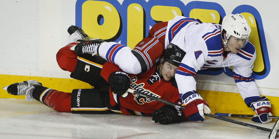 Photo - New York Rangers' Raphael Diaz, right, from Switzerland, crashes over Calgary Flames' Kenny Agostino during the second period of an NHL hockey game in Calgary, Alberta, Friday, March 28, 2014. (AP Photo/The Canadian Press, Jeff McIntosh)