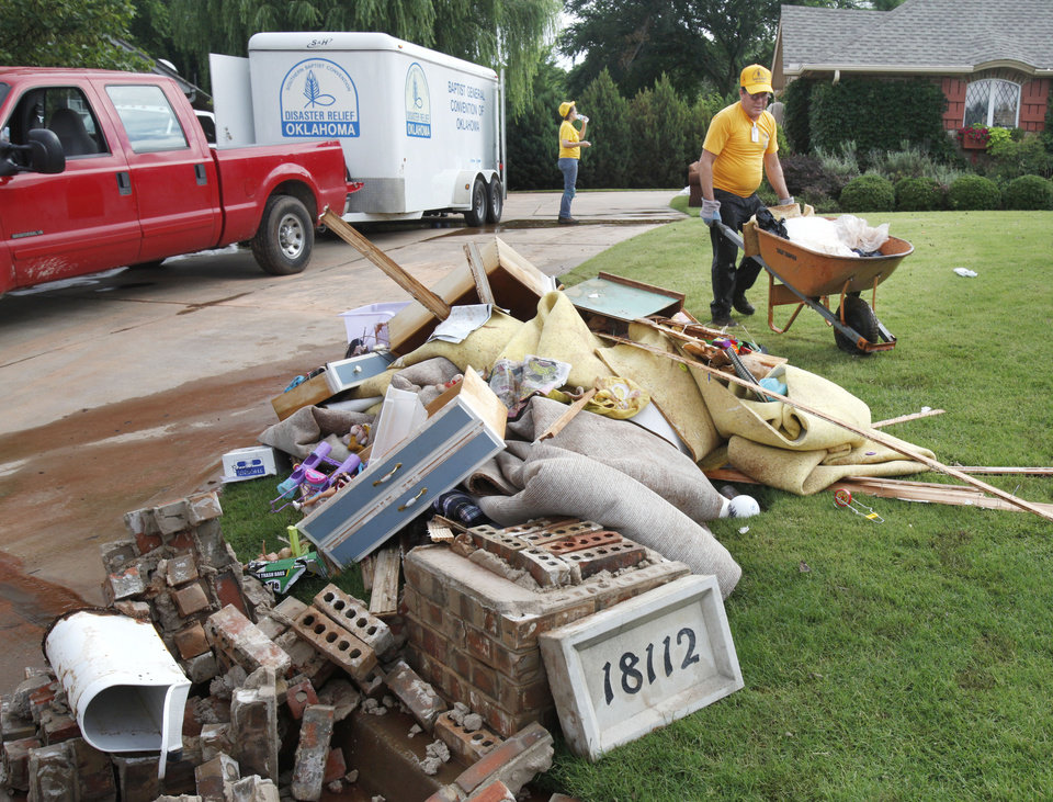 Photo - Blair Quinn, with the Southern Baptist Convention Disaster Relief, helps remove debris from a home in the Palo Verde addition in Edmond, OK, after yesterday's torential rains flooded the neighborhood, Tuesday, June 15, 2010. By Paul Hellstern, The Oklahoman