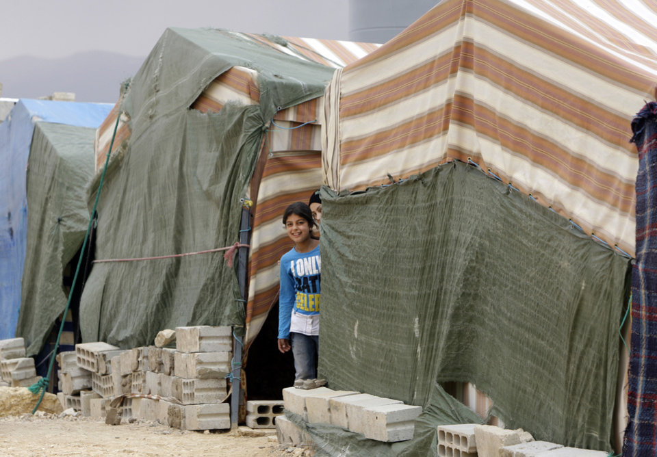 Photo -   In this Tuesday, Oct. 2, 2012 photo, Syrian refugees girls appear through tents at a refugee camp in Arsal, a Sunni Muslim town eastern Lebanon near the Syrian border, has become a safe haven for war-weary Syrian rebels and hundreds of refugee families. Many in Arsal support the rebels, but the town's stand is risking heightened tensions with its Shiite Muslim neighbors in an area controlled by Hezbollah, a militia that backs the Syrian regime. Deepening sectarian rifts are one of the ways in which Syria's 18-month-old conflict is destabilizing an already volatile region. (AP Photo/Bilal Hussein)