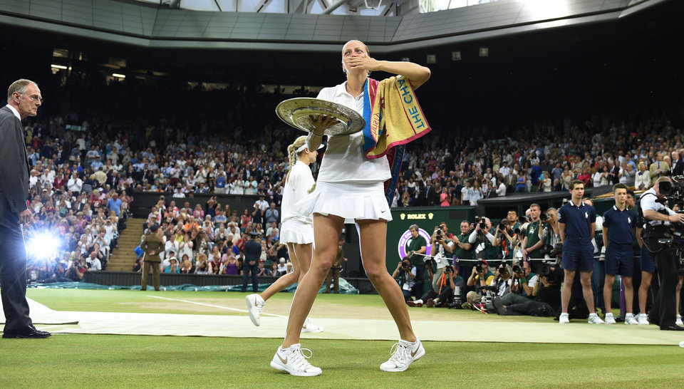 Photo - Petra Kvitova of Czech Republic blows a kiss to the crowd as she holds the trophy after winning the  women's singles final against Eugenie Bouchard of Canada  the All England Lawn Tennis  Championships at Wimbledon, London, Saturday, July, 5, 2014. (AP Photo/Andy Rain, Pool)