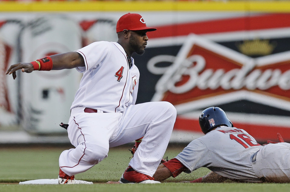 Photo - St. Louis Cardinals' Kolten Wong (16) steals second base as Cincinnati Reds second baseman Brandon Phillips (4) is late with the tag in the first inning of a baseball game, Sunday, May 25, 2014, in Cincinnati. (AP Photo/Al Behrman)
