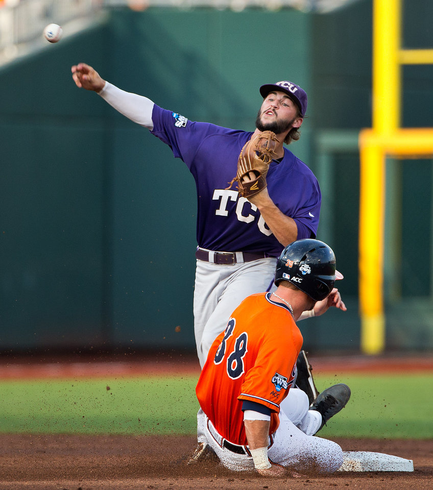 Photo - TCU's Garrett Crain (34), top, turns a double play after tagging out Virginia's Mike Papi (38) at second base to close out the bottom of the first inning of game 8 during the College World Series at TD Ameritrade Park in Omaha, Neb., Tuesday, June 17, 2014. (AP Photo/The Omaha World-Herald, Brendan Sullivan)