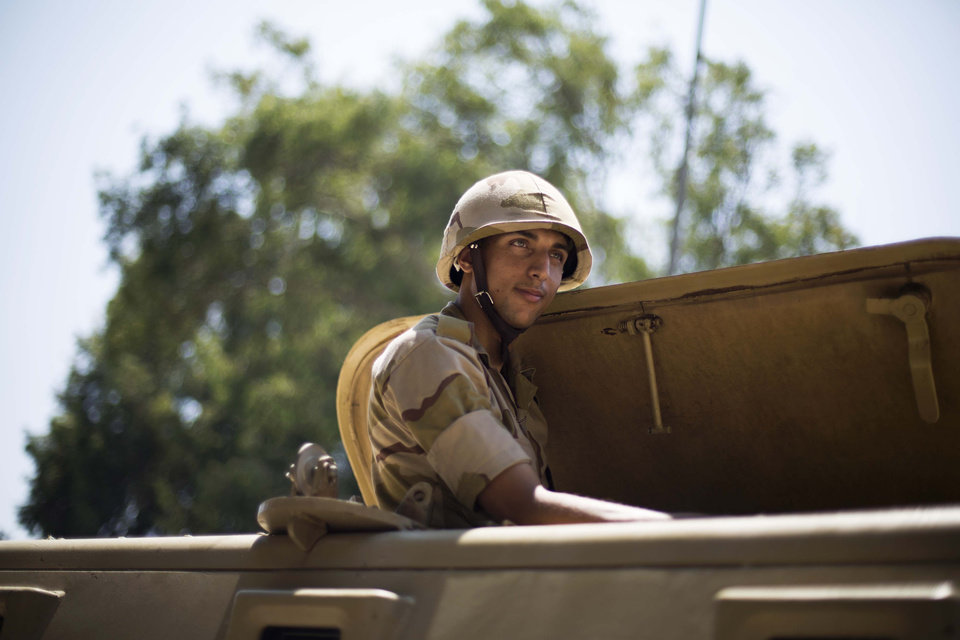 An Egyptian soldier sits in an armored vehicle near Cairo University, where Muslim Brotherhood supporters have gathered to support the country's ousted president Mohammed Morsi in Cairo, Thursday, July 4, 2013. The chief justice of Egypt's Supreme Constitutional Court was sworn in Thursday as the nation's interim president, taking over hours after the military ousted the Islamist President Mohammed Morsi. Adly Mansour took the oath of office at the Nile-side Constitutional Court in a ceremony broadcast live on state television. According to military decree, Mansour will serve as Egypt's interim leader until a new president is elected. A date for that vote has yet to be set. (AP Photo/Manu Brabo)