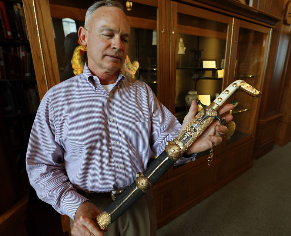 Photo - John Lovett, Director of Special Collections with the Western History Collection shows a ceremonial sword given as a gift by the first king of Saudi Arabia that is part of the in the George C. McGhee collection on Thursday, June 5, 2014 in Norman, Okla.  Photo by Steve Sisney, The Oklahoman