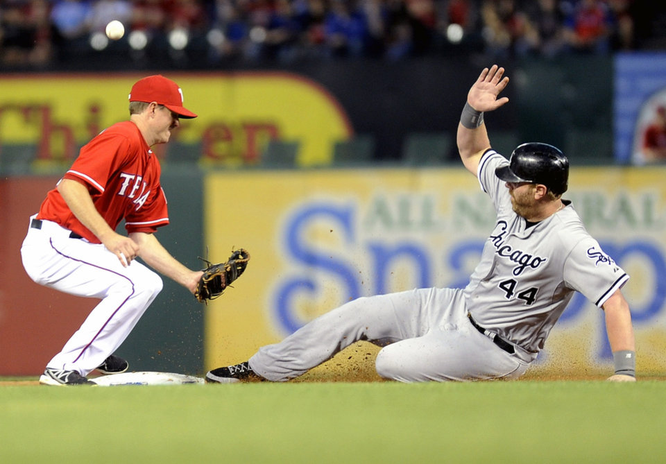 Photo - Chicago White Sox' Adam Dunn (44) steals second base as the throw gets away from Texas Rangers second baseman Josh Wilson, left, in the fourth inning of a baseball game on Saturday, April 19, 2014, in Arlington, Texas. (AP Photo/Matt Strasen)