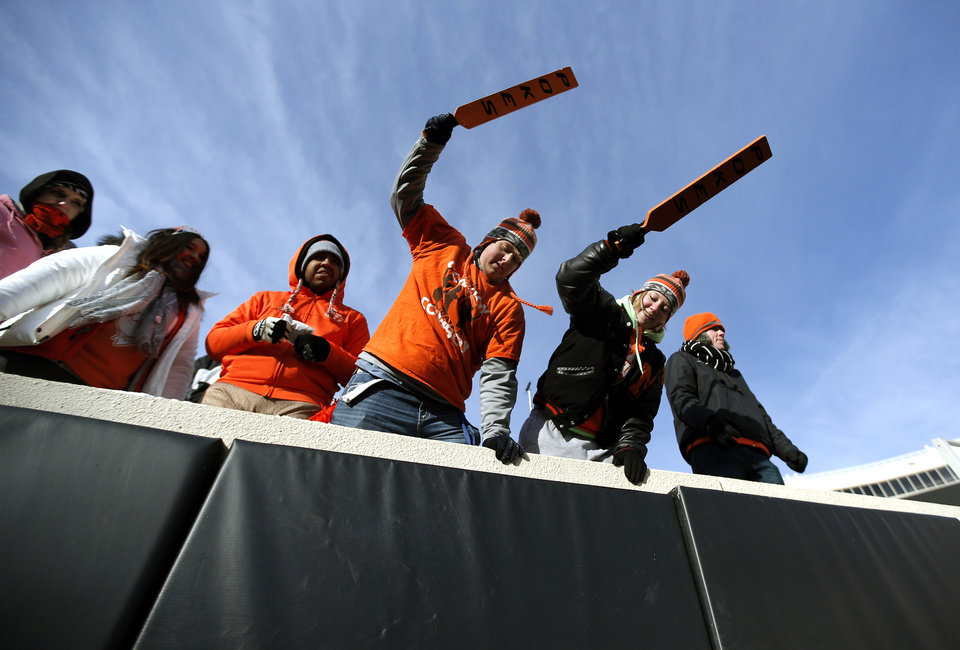 Photo - Tanner Settles, left, and Amanda Slife cheer before the Bedlam college football game between the Oklahoma State University Cowboys (OSU) and the University of Oklahoma Sooners (OU) at Boone Pickens Stadium in Stillwater, Okla., Saturday, Dec. 7, 2013. Photo by Sarah Phipps, The Oklahoman