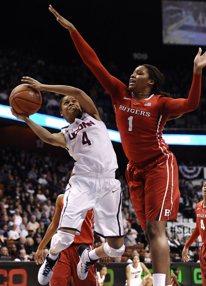 Photo - Connecticut's Moriah Jefferson, left, drives to the basket as Rutgers' Rachel Hollivay, right, defends during the second half of an NCAA college basketball game in the semifinals of the American Athletic Conference women's tournament on Sunday, March 9, 2014, in Uncasville, Conn. Connecticut won 83-57. (AP Photo/Jessica Hill)