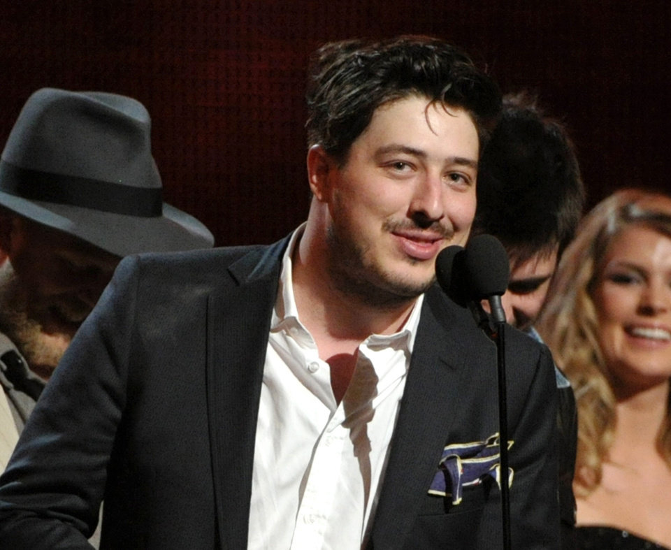 "FILE - This Feb. 10, 2013 file photo shows Marcus Mumford accepting the award on stage for album of the year for ""Babel"" by Mumford & Sons at the 55th annual Grammy Awards in Los Angeles. Paul McCartney and Mumford & Sons are among the headliners for the 2013 Bonnaroo Music & Arts Festival in Manchester, Tenn. The four-day festival, held on a rural 700-acre farm, will be held June 13-16, 2013. (Photo by John Shearer/Invision/AP, file)"