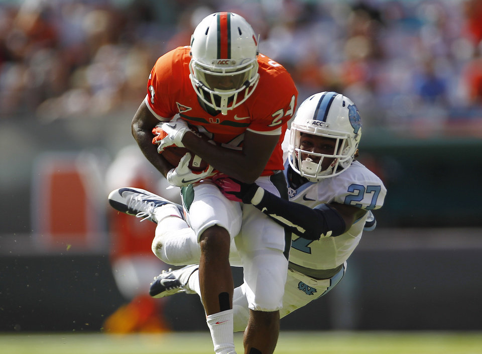 Miami\'s Davon Johnson (24) is stopped by North Carolina\'s Darien Rankin (27) after running for a first down during the first half of a NCAA college football game in Miami, Saturday, Oct. 13, 2012. (AP Photo/J Pat Carter)