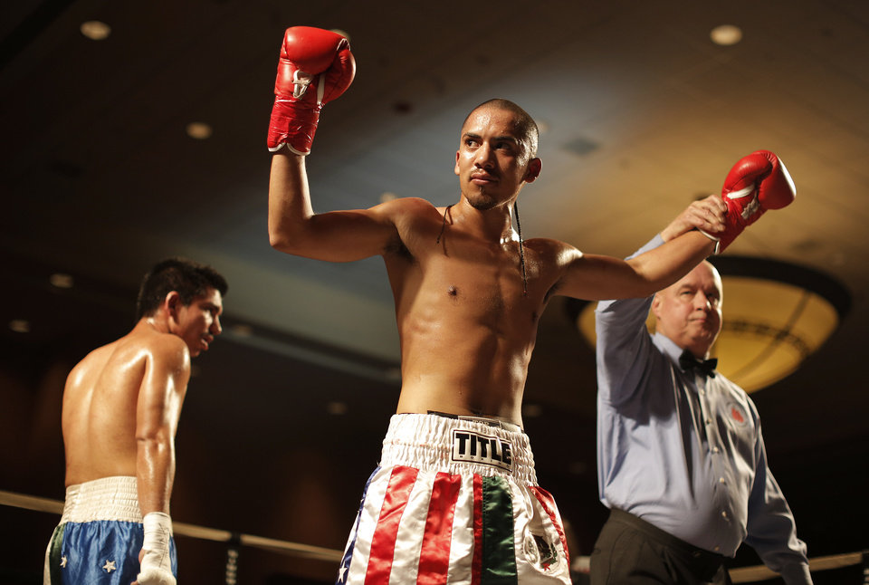 Photo - Vincente Hernandez, of Oklahoma City, wins a fight against Octavio Garay, of Muleshoe, Texas, at the Cox Convention Center in Oklahoma City, Thursday, Sept. 20, 2012.  Photo by Garett Fisbeck, The Oklahoman