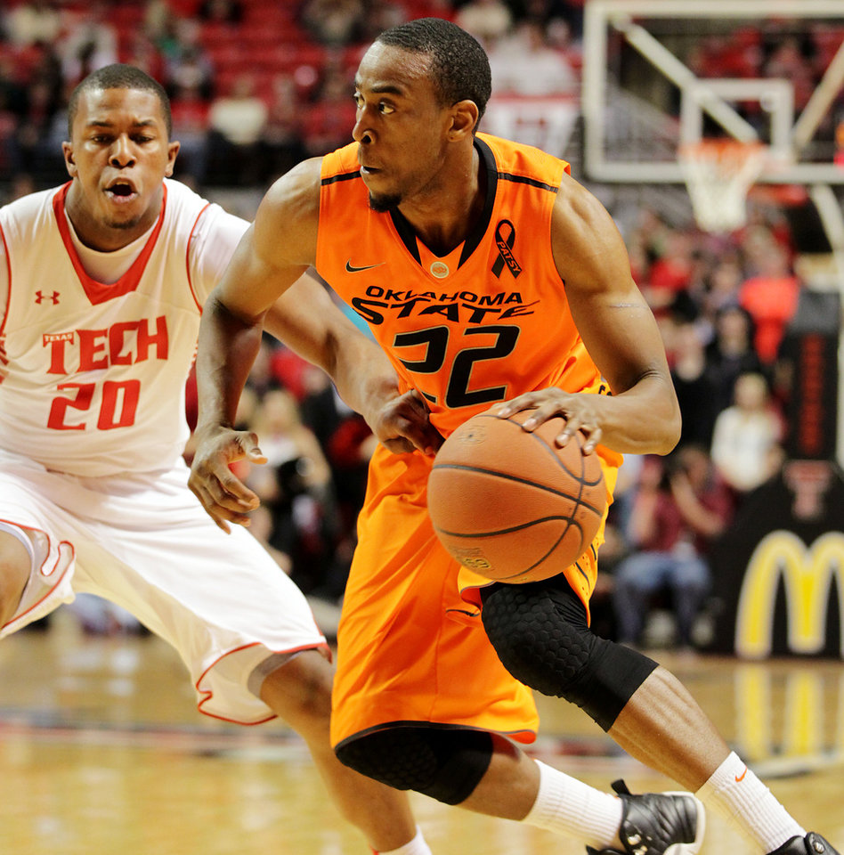 Oklahoma State's Markel Brown (22) drives against Texas Tech's Toddrick Gotcher (20) during their NCAA college basketball game, Wednesday, Feb. 13, 2013, in Lubbock, Texas. (AP Photo/The Avalanche-Journal, Zach Long) ALL LOCAL TV OUT ORG XMIT: TXLUB107