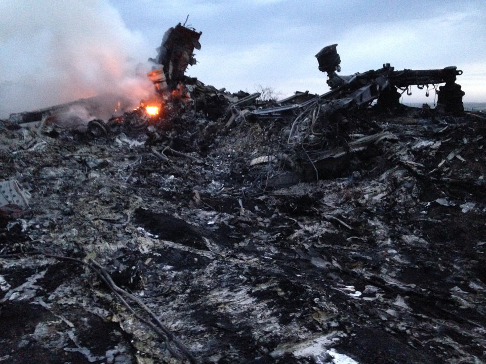 Photo - Smoke rises up at a crash site of a passenger plane, near the village of Grabovo, Ukraine, Thursday, July 17, 2014. A Ukrainian official said a passenger plane carrying 295 people was shot down Thursday as it flew over the country and plumes of black smoke rose up near a rebel-held village in eastern Ukraine. Malaysia Airlines tweeted that it lost contact with one of its flights as it was traveling from Amsterdam to Kuala Lumpur over Ukrainian airspace.  (AP Photo/Dmitry Lovetsky)