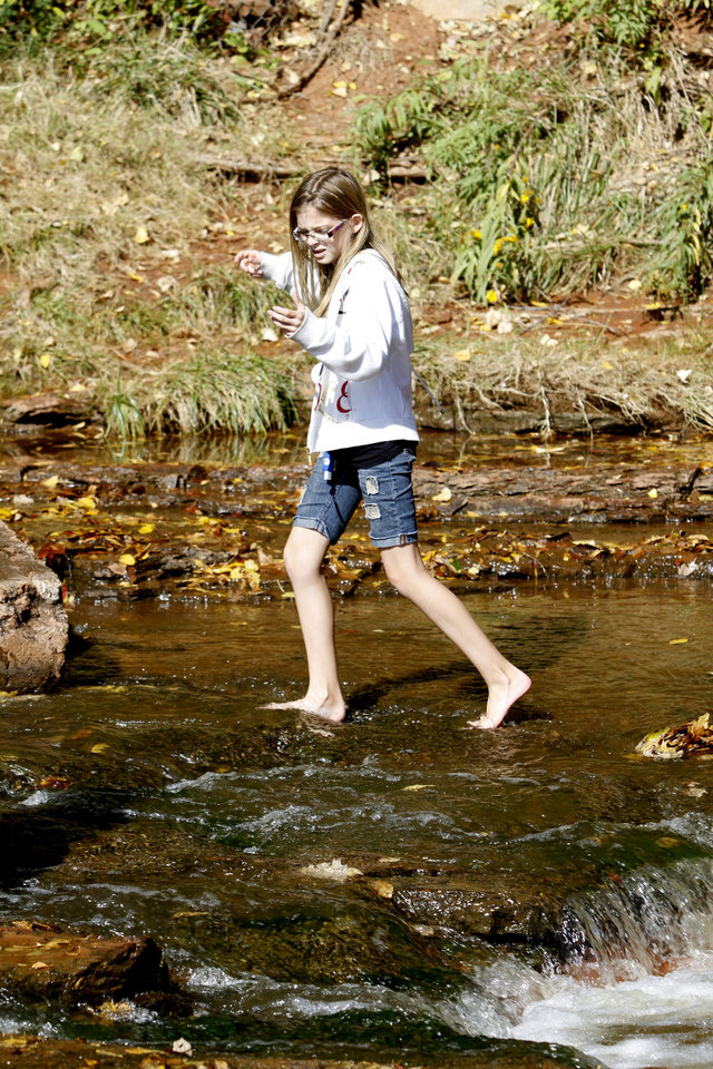 Emily Nolin, 10, walks across a creek at Martin Park Nature Center in Oklahoma City in October. Plans to make the park more accessible to people with disabilities have proved controversial.  Photo by Steve Gooch, The Oklahoman Archives