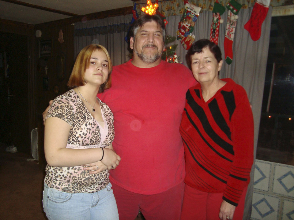 Photo - FEBRUARY 10, 2009 / LONE GROVE / TORNADO VICTIMS / DEATH / SUSAN FAMBROUGH / WILLIAM FAMBROUGH: Kaylee Fambrough, 13, lost both parents - Susan Gail Fambrough, 54; and William Vincent Fambrough, 48 - to a tornado Tuesday night and barely escaped with her own life. This is the three of them celebrating Christmas last year.  Lone Grove, OK, Thursday, Feb. 12, 2009 ORG XMIT: KOD