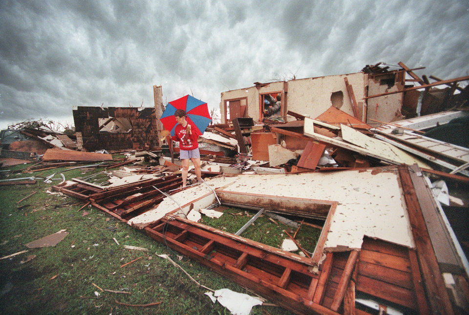 MAY 3, 1999 TORNADO: Tornado victims, damage: Julie Dike and husband Roy (in window in background) in the remains of their house at 5908 SE 9th st in Midwest City. They survived the tornado with their son David, 26, by getting  in a hall closet. They were uninjured.
