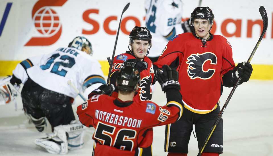 Photo - Calgary Flames' Joe Colborne, right, celebrates his goal with teammate Tyler Wotherspoon, left, and Curtis Glencross as San Jose Sharks goalie Alex Stalock picks himself up during second period NHL hockey action in Calgary, Monday, March 24, 2014. (AP Photo/The Canadian Press, Jeff McIntosh)