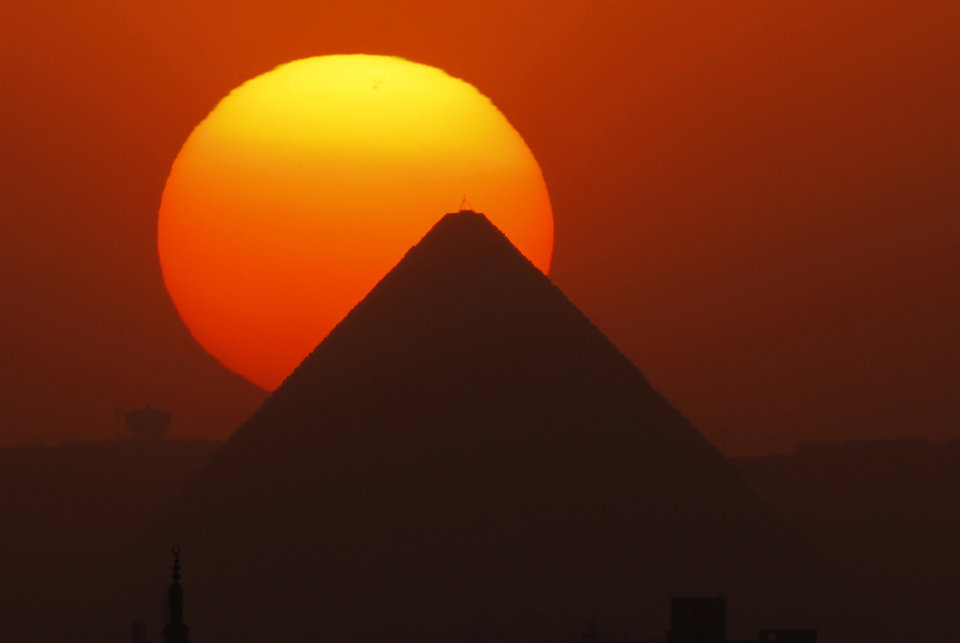 Photo - The sun sets behind the Great Pyramid in Giza, Egypt, Friday, April 26, 2013. Elsewhere, dozens of mostly masked protesters are hurling stones and firebombs in clashes with riot police at Egypt's presidential palace in a Cairo suburb. Protests have become a weekly routine in Egypt, as the country has plunged in turmoil during most of the past two years since 2011 uprising which ousted longtime president Hosni Mubarak out of power.  (AP Photo/Amr Nabil)