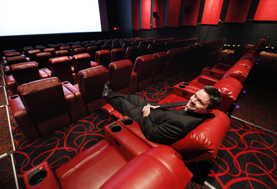 Ryan Noonan, a spokesman for AMC Theatres, demonstrates the new power reclining chairs at the Penn Square Mall theater. <strong>PAUL B. SOUTHERLAND - PAUL B. SOUTHERLAND</strong>
