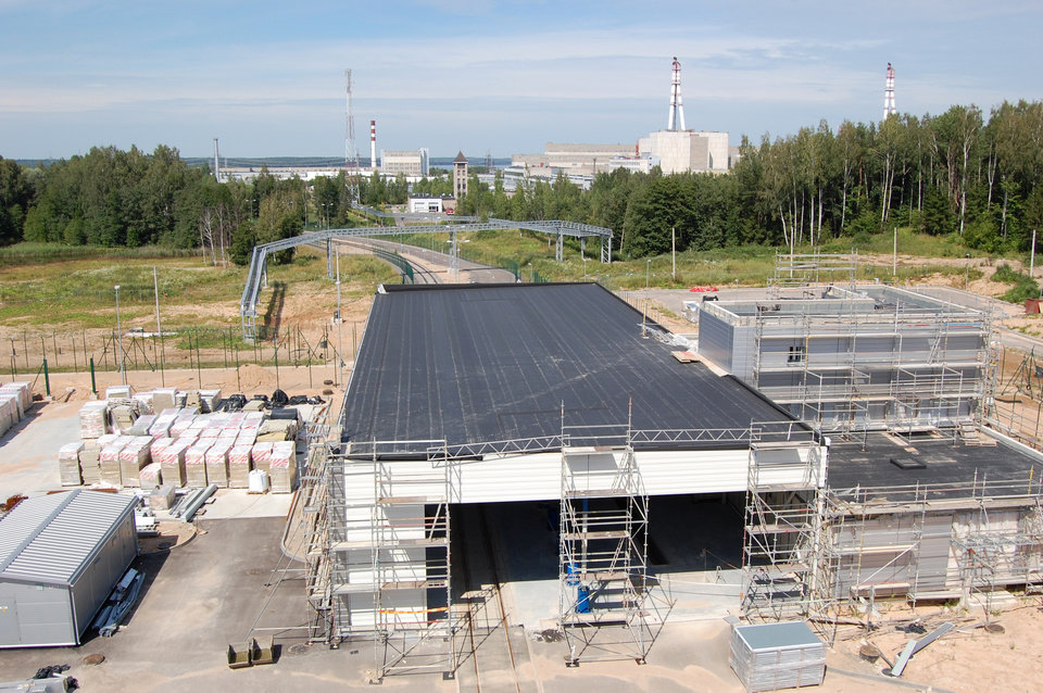 ADVANCE FOR USE SUNDAY, NOV. 18, 2012 AND THEREAFTER - This July 2012 photo shows the gatehouse of the partially-completed nuclear storage facility in Ignalina, Lithuania. Three years after the nuclear plant was shut down due to safety concerns, there is still nuclear fuel inside one of the two reactors. The temporary storage facilities for spent fuel and radioactive waste are four years behind schedule. The problems have prompted threats from the European Union to sever funding and raising concerns that the facility will be around for years, possibly decades, longer than planned. The giant ventilation stacks in the background are part of the nuclear power plant. (AP Photo/Gary Peach)