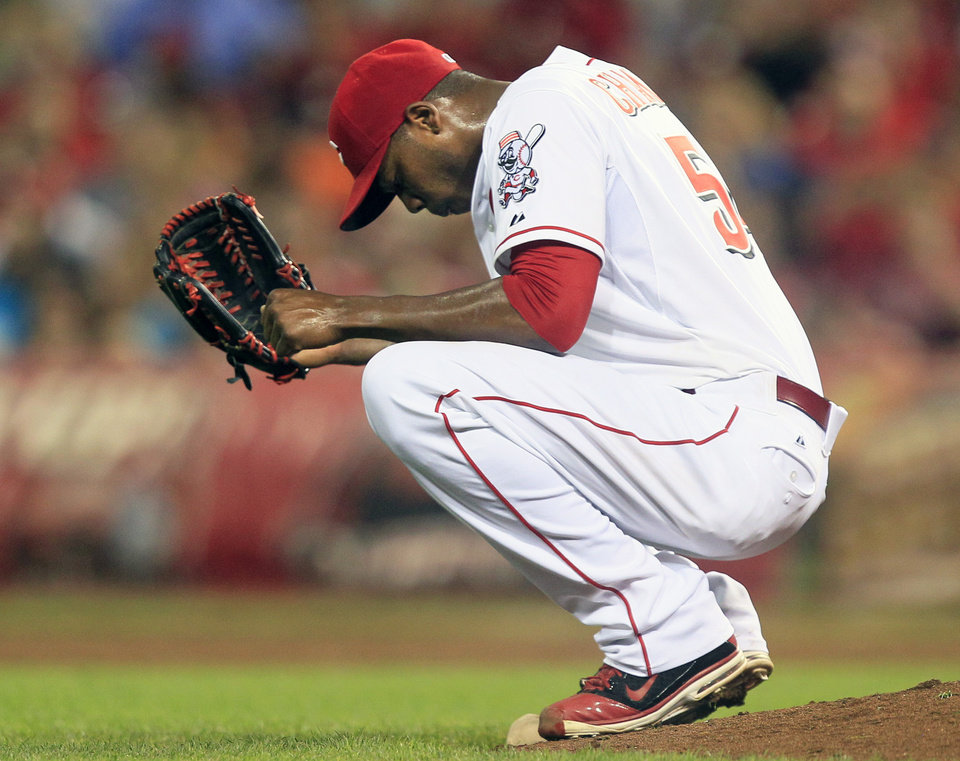 Photo -   Cincinnati Reds relief pitcher Aroldis Chapman squats behind the mound after giving up a three-run home run to Houston Astros' Matt Dominguez in the ninth inning of a baseball game, Friday, Sept. 7, 2012, in Cincinnati. Houston won 5-3. (AP Photo/Al Behrman)